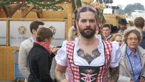 L'uomo ubriaco in una via vestita in un dirndl femminile sta divertendosi alla Baviera di Oktoberfest Movimento lento video d archivio