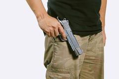 L'uomo in un cammuffamento ansima giudicando una pistola isolata su fondo bianco Fotografia Stock Libera da Diritti