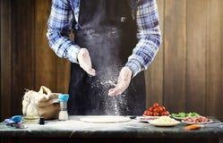 L'uomo in un grembiule che prepara una pizza, impasta la pasta e mette il ingr Fotografie Stock