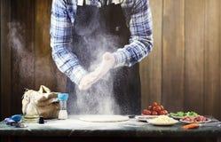L'uomo in un grembiule che prepara una pizza, impasta la pasta e mette il ingr Fotografia Stock