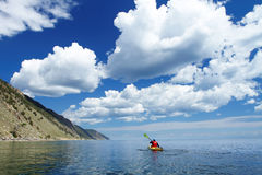 L'uomo in un kajak attraversa il lago Baikal Fotografie Stock