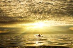 L'uomo in un kajak su un tramonto Immagini Stock
