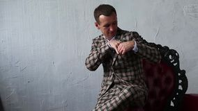 L'uomo in un vestito del mantello piega un fazzoletto in sua tasca archivi video