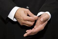 L'uomo in un vestito di affari corregge un manicotto immagine stock