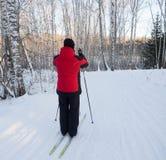 L'uomo in un vestito rosso funziona sugli sci nel legno dell'inverno Cresta co del ghiaccio Fotografie Stock