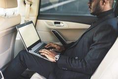 L'uomo in un vestito scrive sul computer portatile nel salone di un'automobile costosa con l'interno di cuoio immagine stock libera da diritti