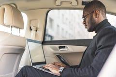 L'uomo in un vestito scrive sul computer portatile nel salone di un'automobile costosa con l'interno di cuoio immagine stock