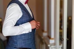 L'uomo in una camicia bianca ed in una maglia grigia fissa i bottoni davanti allo specchio Sposo in vestito grigio e legame che s fotografia stock