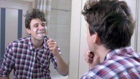 L'uomo in una camicia di plaid con postumi di una sbornia sta radendosi esaminando lo specchio nel bagno archivi video