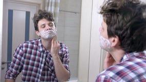 L'uomo in una camicia di plaid con postumi di una sbornia sta radendosi esaminando lo specchio nel bagno video d archivio
