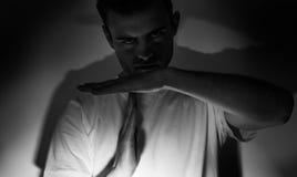L'uomo in una maglietta bianca che mostra il tempo fuori firma con le mani, su un fondo bianco alla luce scura fotografia stock