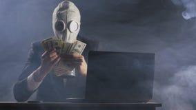L'uomo in una maschera antigas di un in un ufficio ripieno di fumo racconta i soldi stock footage