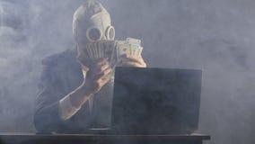 L'uomo in una maschera antigas di un in un ufficio ripieno di fumo racconta i soldi video d archivio