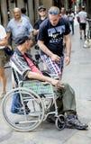 L'uomo in una sedia a rotelle chiede aiuto ai passanti nel quarto gotico Fotografie Stock