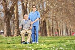 L'uomo in una sedia a rotelle ed il maschio curano la posa nel parco Fotografie Stock Libere da Diritti