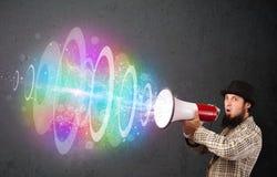 L'uomo urla in un altoparlante ed il fascio di energia variopinto esce Immagine Stock Libera da Diritti