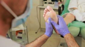 L'uomo usa le sue punte delle dita per massaggiare il fondo di un piede del ` s della donna stock footage