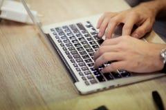 L'uomo utilizza il computer portatile Immagine Stock