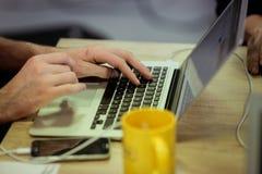 L'uomo utilizza il computer portatile Fotografie Stock Libere da Diritti