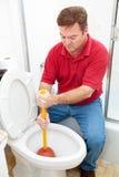 L'uomo utilizza il tuffatore sulla toilette ostruita fotografie stock libere da diritti
