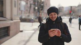 L'uomo utilizza lo smartphone che cammina in una via della città