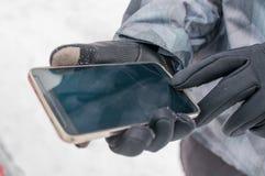 L'uomo utilizza lo smartphone nell'inverno Fotografie Stock Libere da Diritti