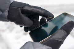 L'uomo utilizza lo smartphone nell'inverno Fotografia Stock
