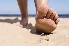 L'uomo va sulla spiaggia e sul rischio di fare un passo su una scheggia di vetro da bottiglia rotto Fotografie Stock