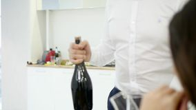 L'uomo versa due vetri di champagne per celebrare entrare nella nuova casa con l'amica stock footage