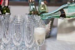 L'uomo versa il champagne in bicchieri di vino immagini stock libere da diritti