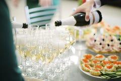L'uomo versa il champagne in un vetro da una bottiglia fotografia stock
