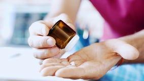 L'uomo versa le pillole dalla bottiglia sulla sua mano Concetto di sanità e della medicina video d archivio