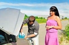 L'uomo versa un liquido all'automobile Fotografie Stock Libere da Diritti