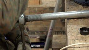 L'uomo in vestiti ed in guanti speciali da un utensile speciale esegue il filo di rinforzo del metallo di taglio e di lubrificazi archivi video