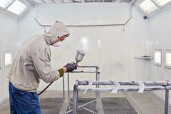 L'uomo in vestiti protettivi lavora nella cabina di verniciatura a spruzzo fotografia stock