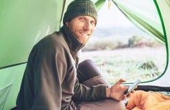 L'uomo vestito caldo del viaggiatore barbuto utilizza il suo telefono cellulare fotografia stock libera da diritti