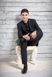 L'uomo in vestito che si siede sulla sedia con le gambe ha attraversato allo studio fotografie stock libere da diritti