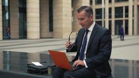 L'uomo in vestito convenzionale lavora al computer portatile stock footage
