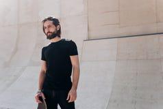 L'uomo vestito nell'abbigliamento casual alla moda che tiene pattino nei suoi supporti della mano in un parco del pattino accanto fotografie stock