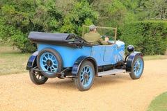 L'uomo in vestito sta conducendo la vecchia automobile del temporizzatore a Beaulieu in Inghilterra di estate Immagine Stock