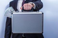 L'uomo in vestito tiene la cartella del metallo con i dollari fotografie stock