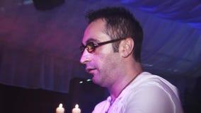 L'uomo in vetri gioca sui tamburi di bongo sul partito in night-club riflettori incoraggiare intrattenimento video d archivio