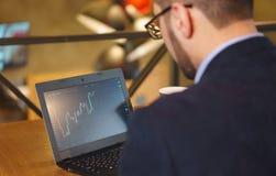 L'uomo in vetri guarda il grafico in aumento di scambio sul computer portatile Immagine Stock