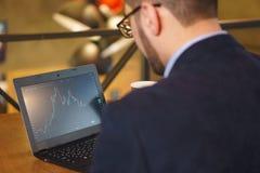 L'uomo in vetri guarda il grafico di caduta di scambio sul computer portatile Fotografie Stock