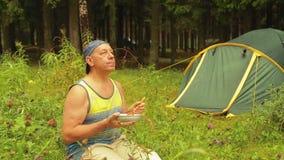 L'uomo vicino alla tenda nel legno sta avendo prima colazione video d archivio