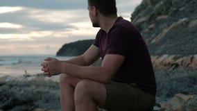 L'uomo viene al lago a rilassarsi la seduta sulla spiaggia della roccia all'aperto video d archivio