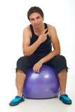 L'uomo vittorioso si siede sulla sfera dei pilates Immagine Stock