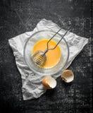 L'uovo battuto in una ciotola con sbatte su carta fotografie stock libere da diritti