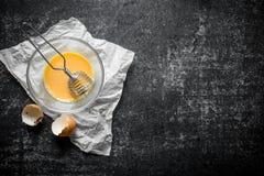 L'uovo battuto in una ciotola con sbatte su carta immagini stock libere da diritti