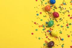 L'uovo di cioccolato di Pasqua con l'esplosione variopinta delle caramelle e dei dolci su giallo ha colorato il fondo Fotografie Stock Libere da Diritti